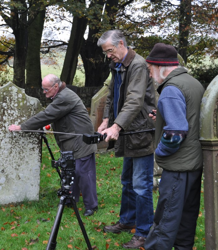 Members of the Embsay with Eastby Research Group conduct RTI photography on a gravestone.