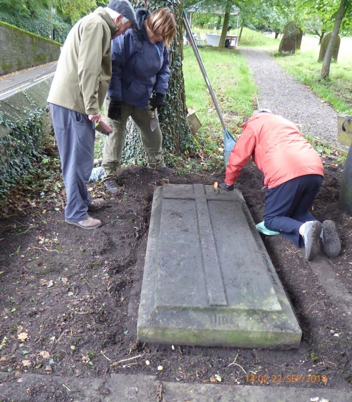 Three members of the Friends of Raikes Road Burial Ground examine a ledger stone.