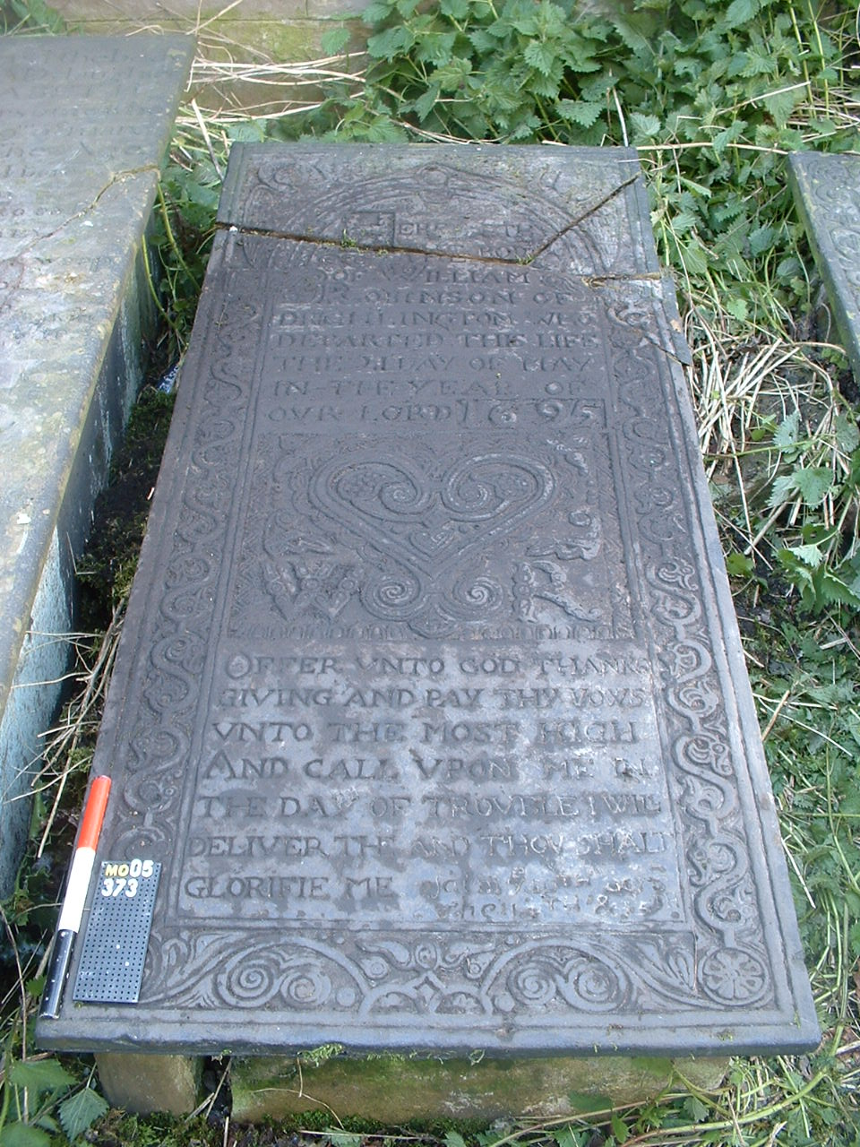 A tombstone with a heart motif